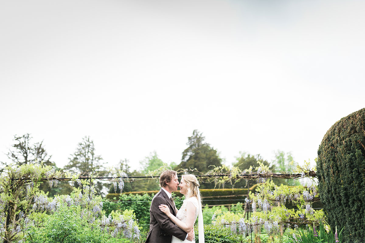 bride and groom kissing in the rain in gardens at Murthly Castle in Perthshire
