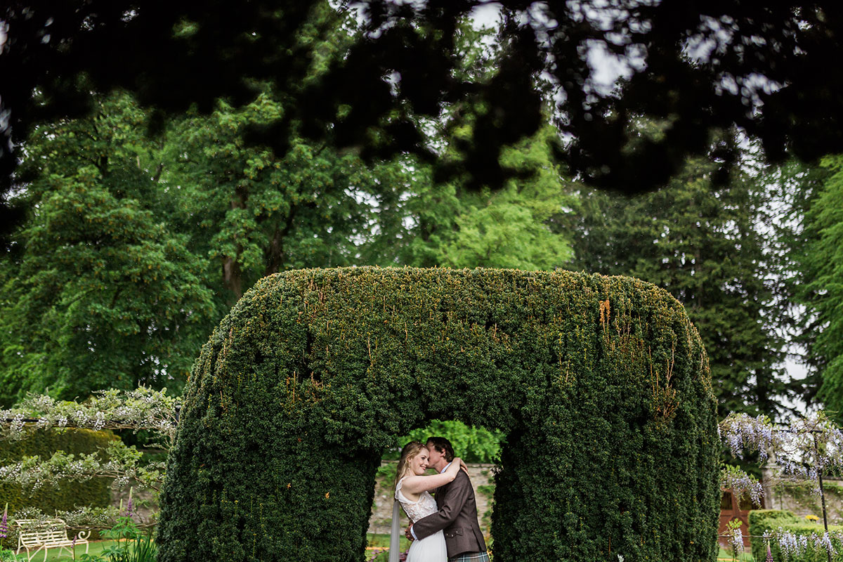 bride and groom kissing under hedge archway in garden at Murthly Castle