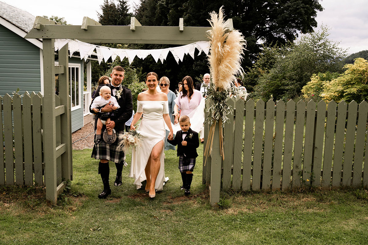 bride and groom with two young sons walking through pampas grass archway at their farm wedding in Perthshire