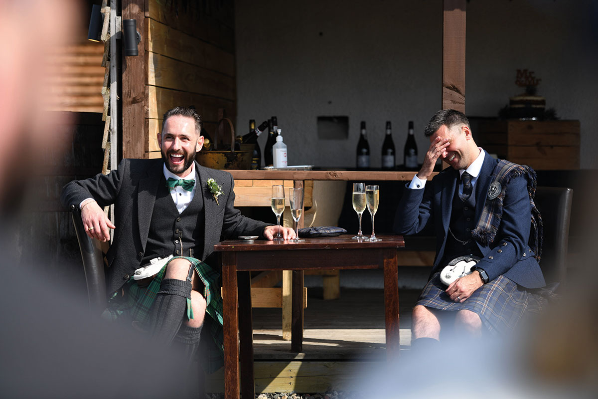two grooms seated at table outside the Gathering laughing and drinking champagne