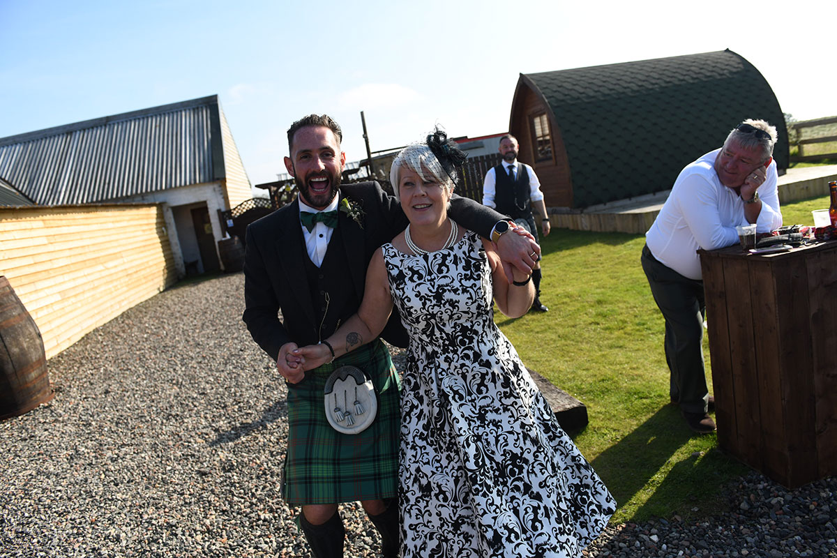 groom dancing Gay Gordon ceilidh dance with female guest outside The Gathering