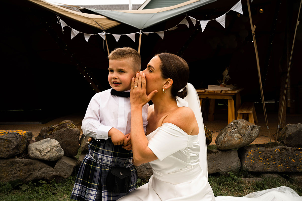 bride whispering in ear of son outside teepee at Perthshire wedding