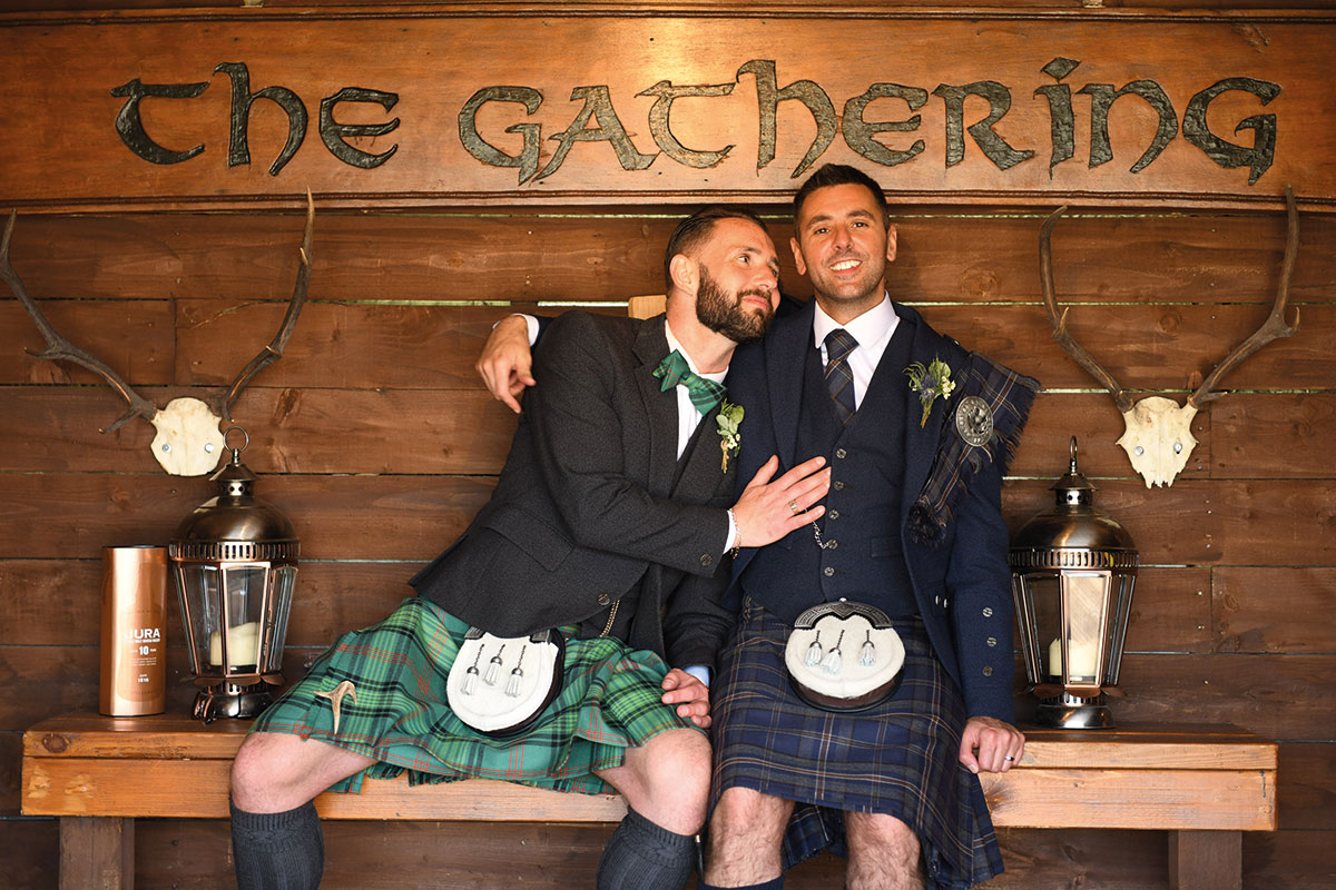 newlywed grooms posing seated at The Gathering sign