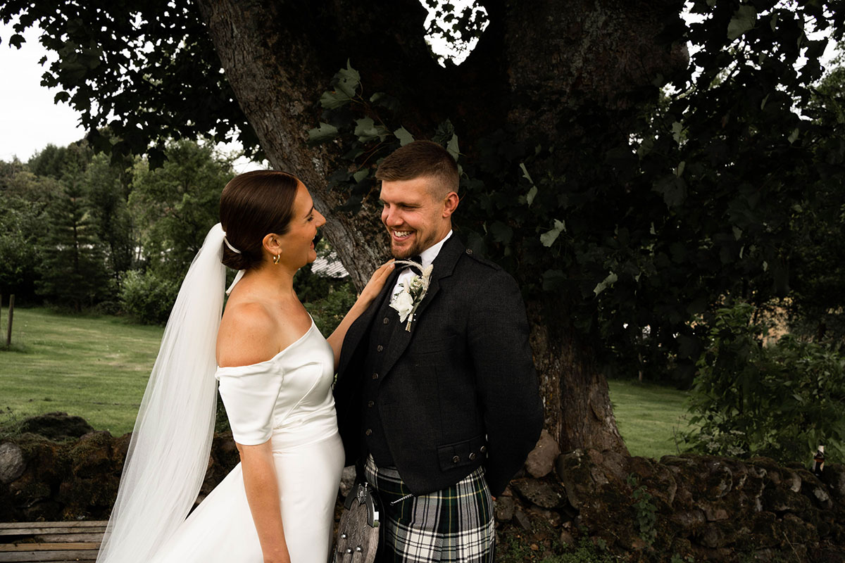 bride and groom smiling at each other standing by a tree