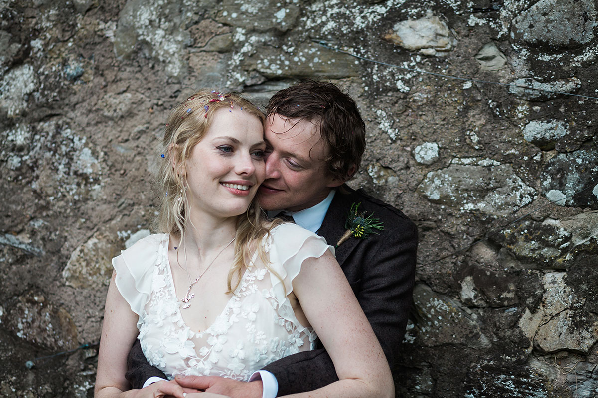 groom nuzzling bride standing against wall in the gardens at Murthly Castle