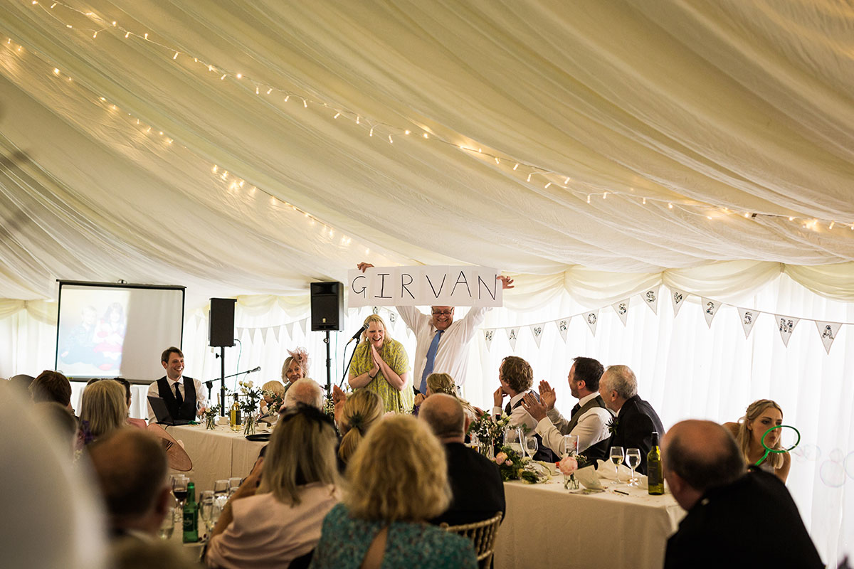 man holding up sign reading 'GIRVAN' during wedding speech in a marquee while guests watch on