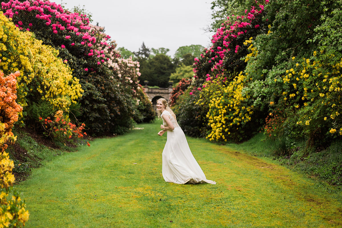 bride running in garden at Murthly Castle and laughing with colourful bushes