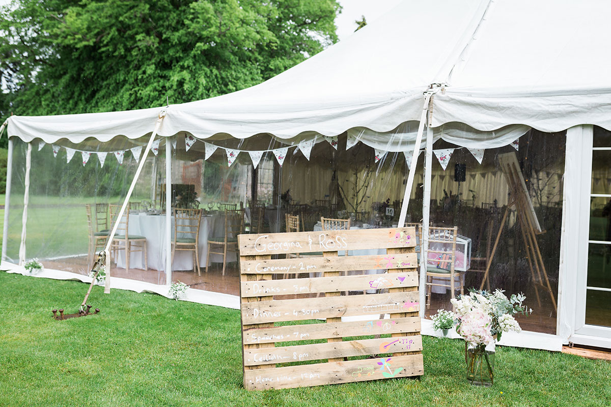 exterior of wedding marquee at Murthly Castle with bunting and wooden pallet order of wedding day