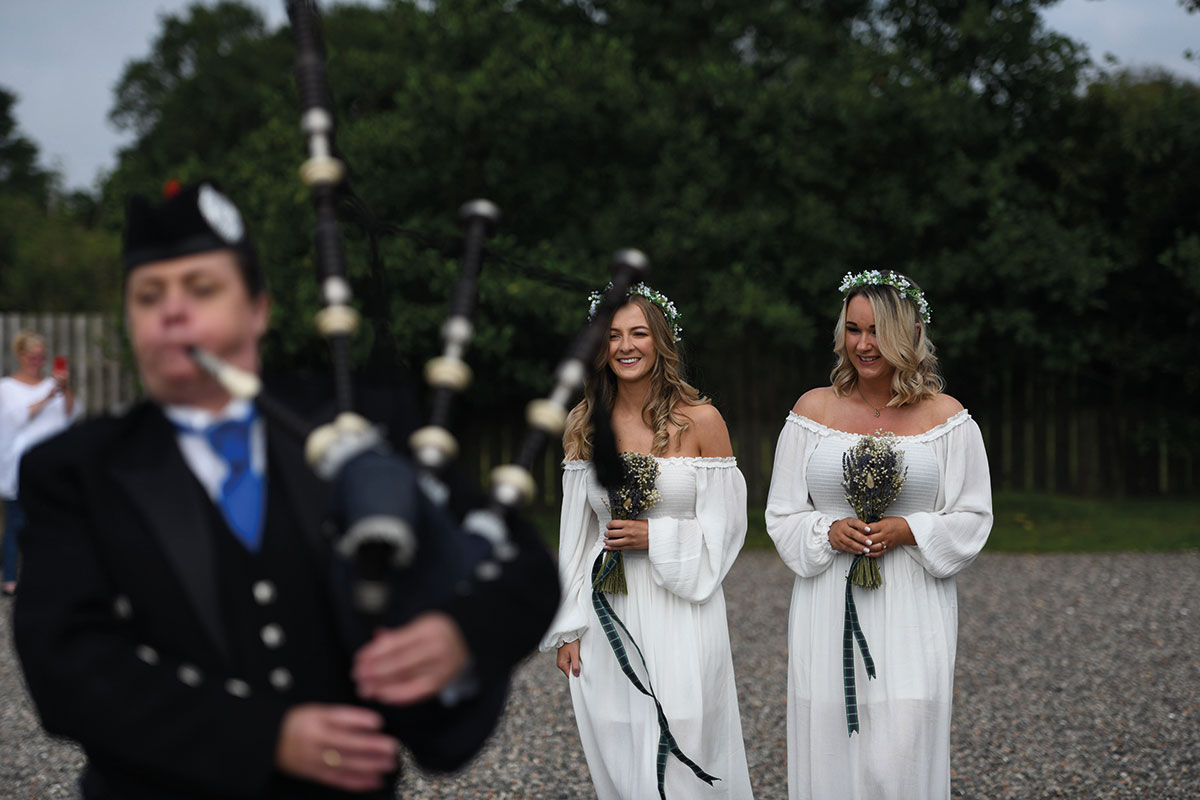 two bridesmaids wearing white off-shoulder dresses and floral crowns at The Gathering with bagpiper