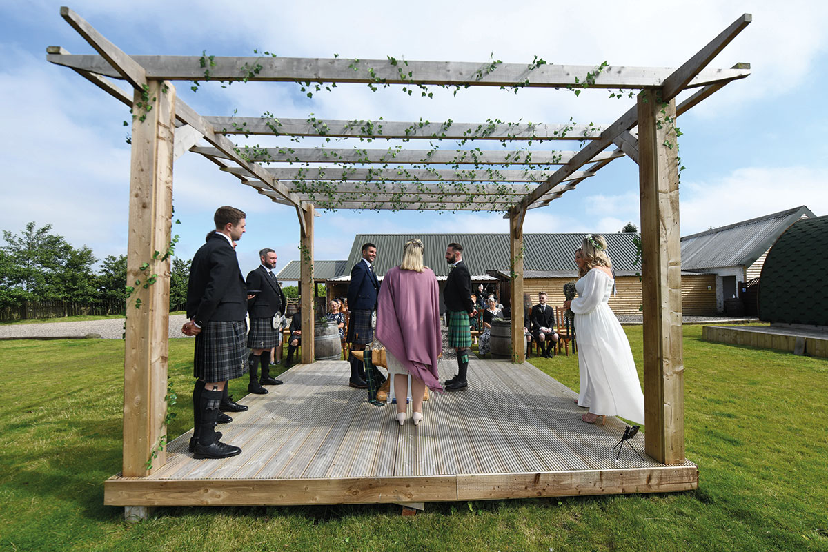 outdoor same sex wedding ceremony under wooden canopy at The Gathering