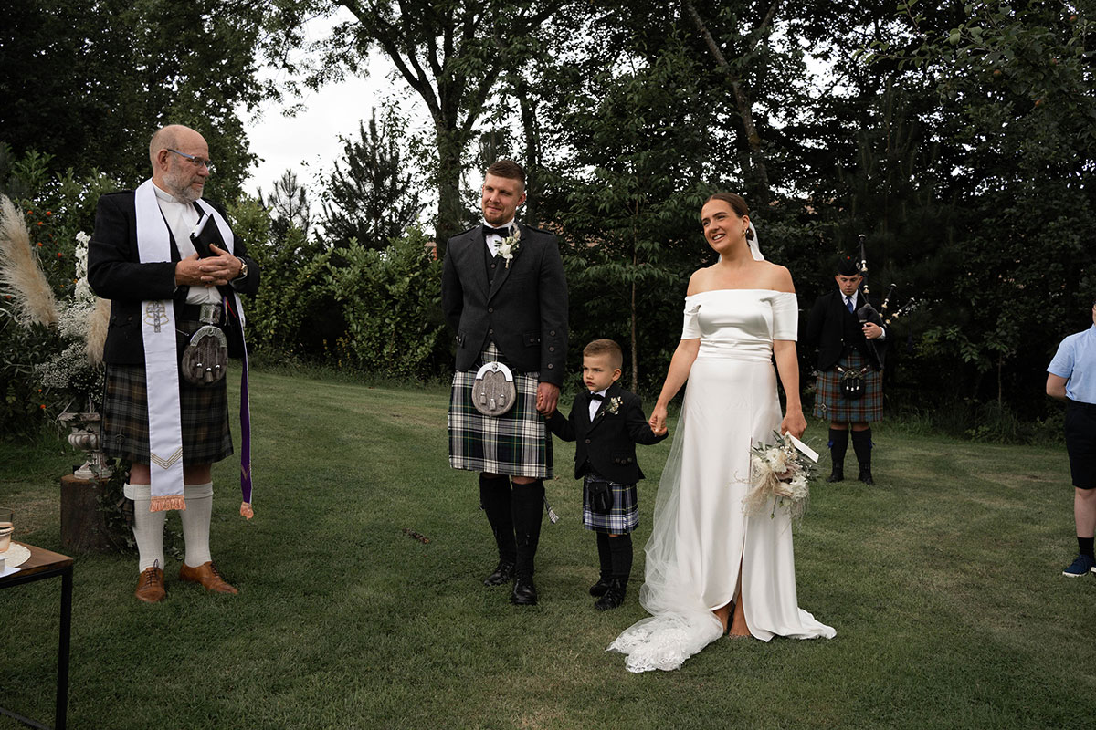 bride and groom holding hands with son in front of minister at outdoor Perthshire farm wedding