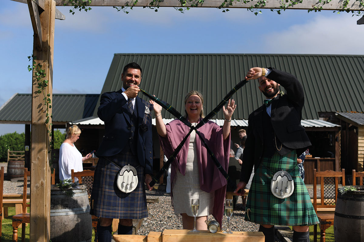 two grooms' hands completed hand fasting ceremony with tartan ribbon
