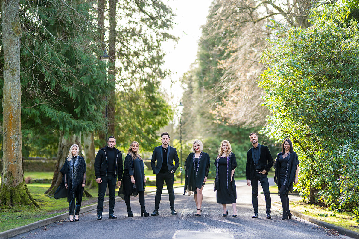 GeO Gospel Choir standing on a road surrounded by trees