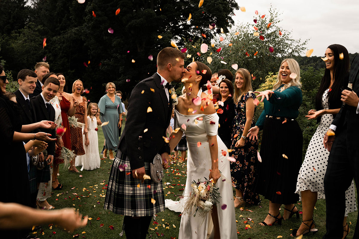 bride and groom kissing while being showered in petal confetti at outdoor Perthshire tipi wedding