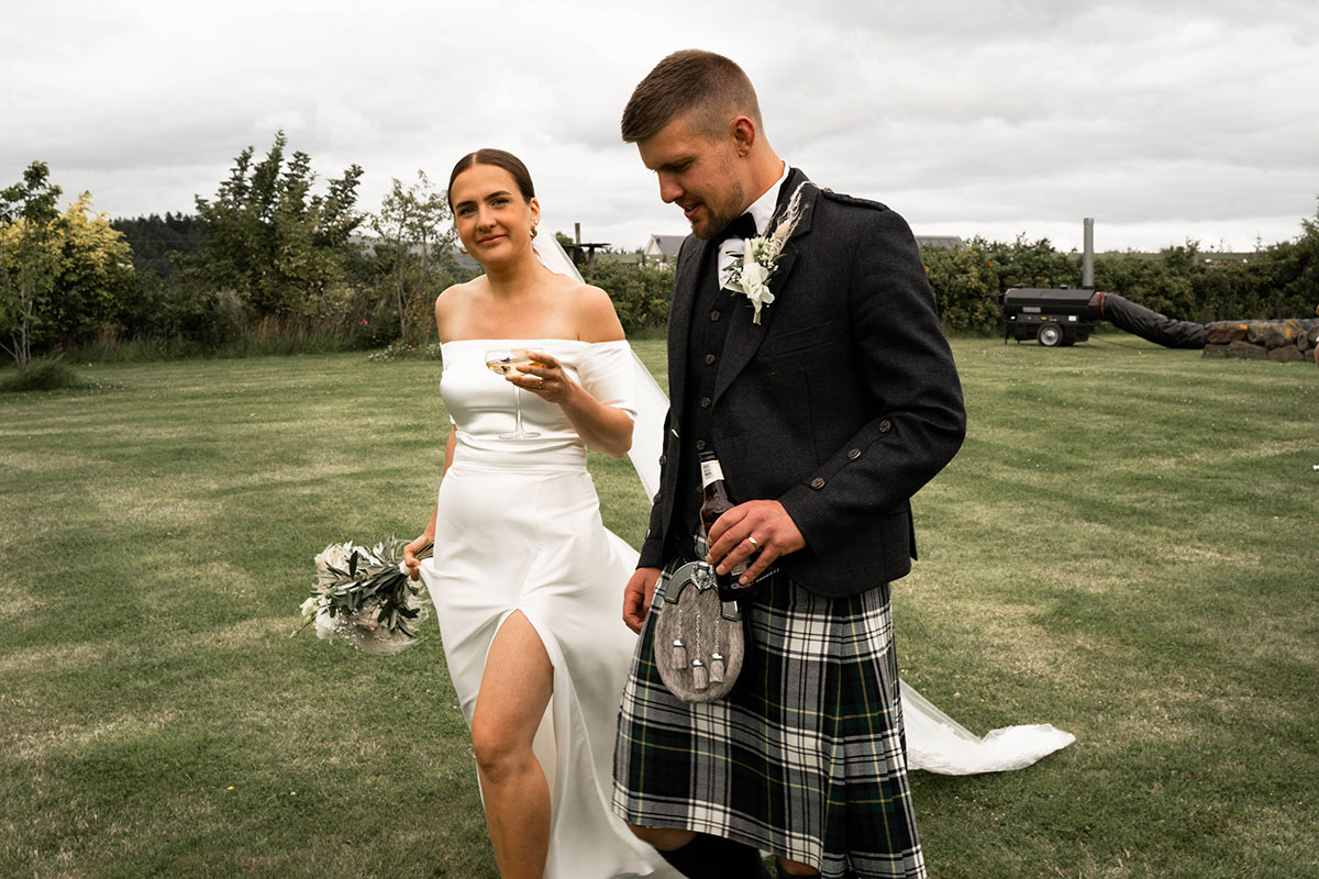 bride and groom walking on lawn carrying drinks at Perthshire tipi farm wedding