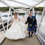 bride and groom walking holding hands on jetty at Loch Lomond with boats in background