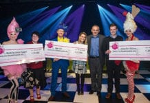 Neil Turton, chief executive of Nisa, third right, and artists at the organisation's Stoneleigh Park dinner present charity cheques to Age UK, Macmillan Cancer Support and Action For Children.