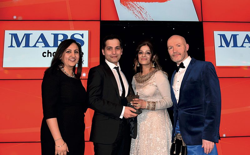 Bep Dhaliwal, trade communications manager, Mars Chocolate UK, left, and awards event host Craig Hill, right, present the Community Champion Award to Asif Akhtar and Abada Akhtar of Smeaton Stores, Kirkcaldy.