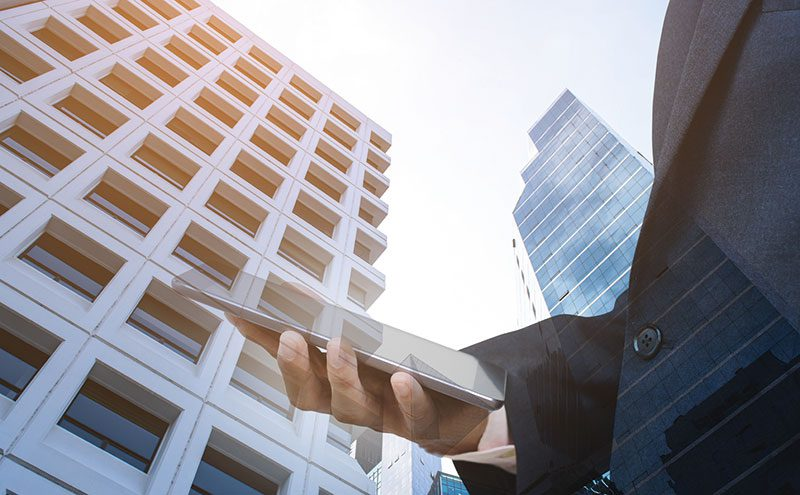 Man holding phone in front of tall building