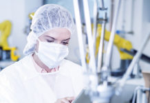 Woman in factory using tablet with robot handling cookies